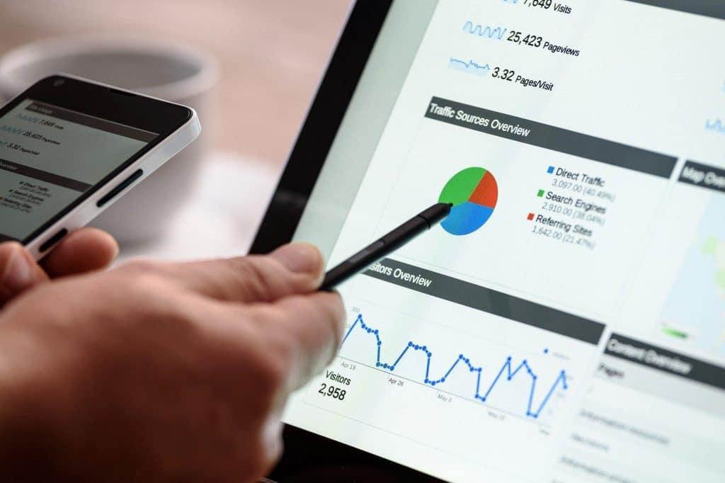 Main tenant un smartphone et pointant avec un stylo un graphique sur un écran d'ordinateur portable.