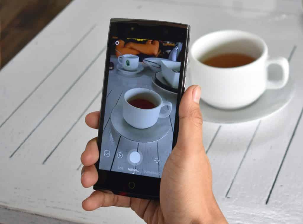 Personne qui prend en photo une tasse de thé grâce à son smartphone.