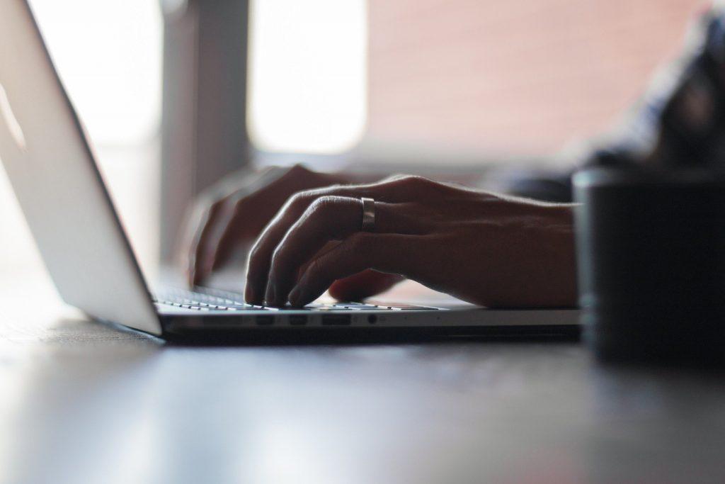 Personne écrivant sur le clavier de son ordinateur portable.