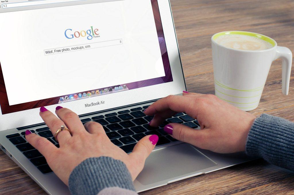 Femme écrivant sur son clavier d'ordinateur pour faire une recherche Google.