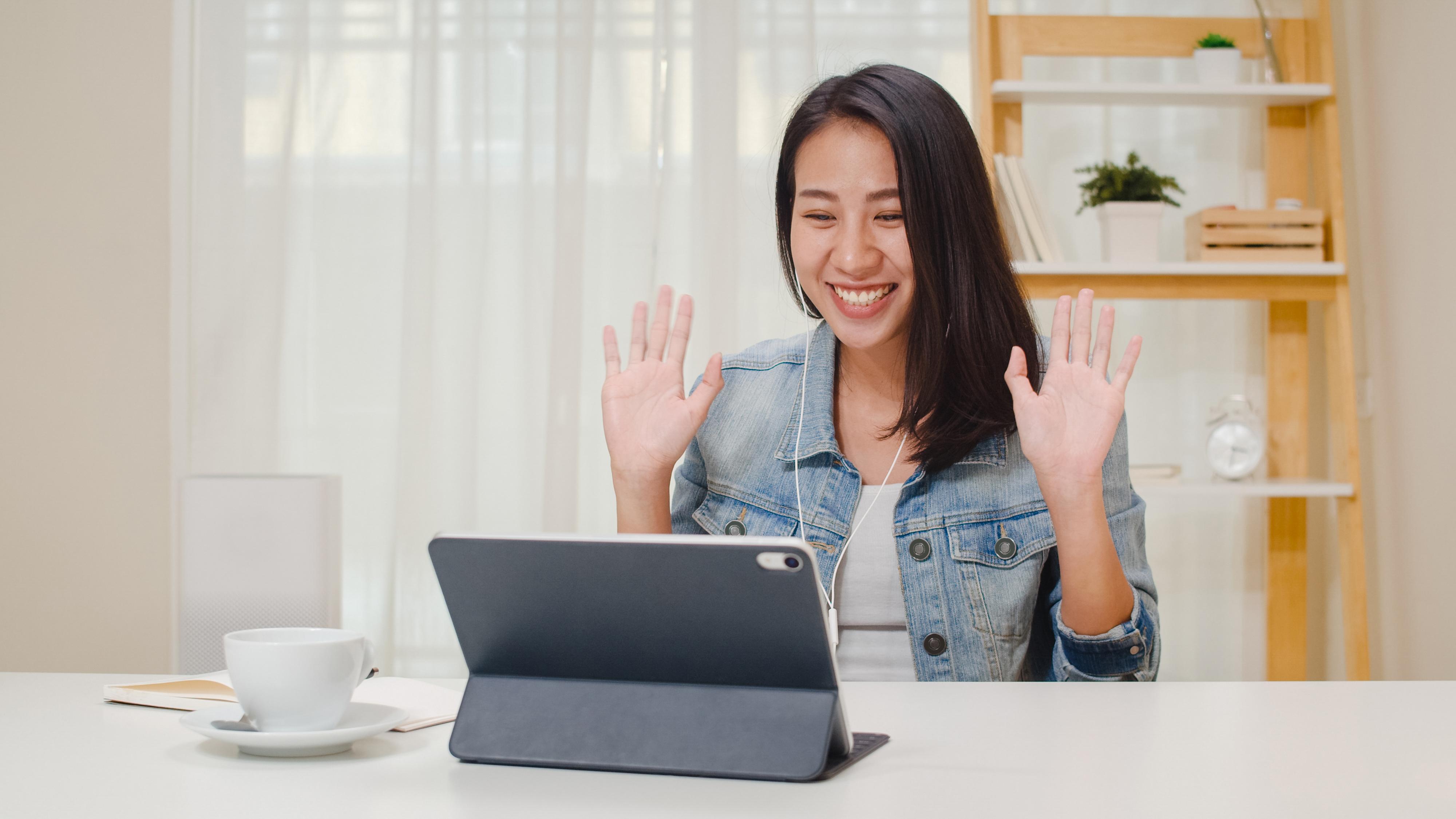 Jeune femme utilisant une tablette tactile pour faire une visioconférence.