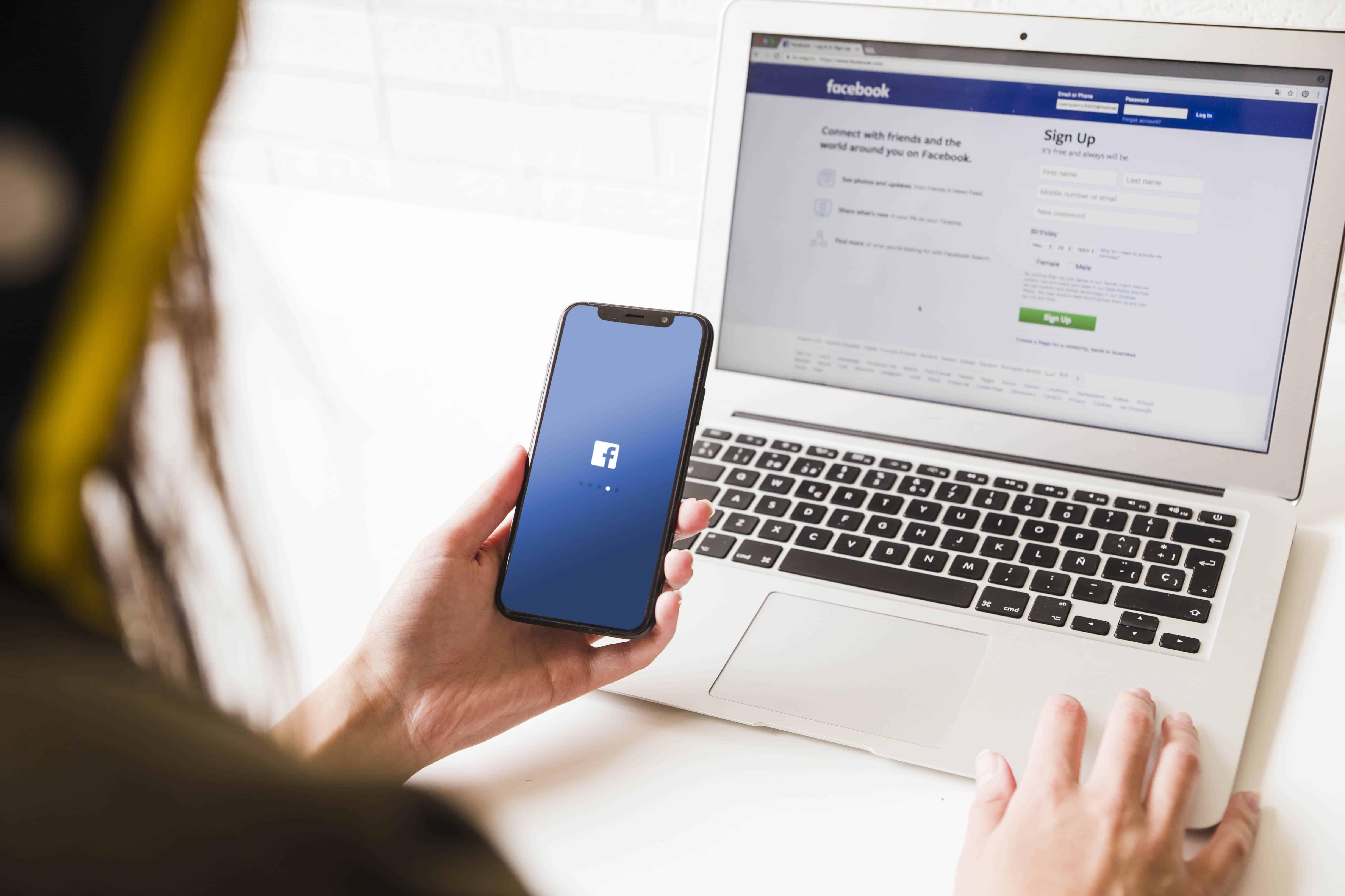 Jeune femme utilisant un smartphone pour se connecter sur Facebook.