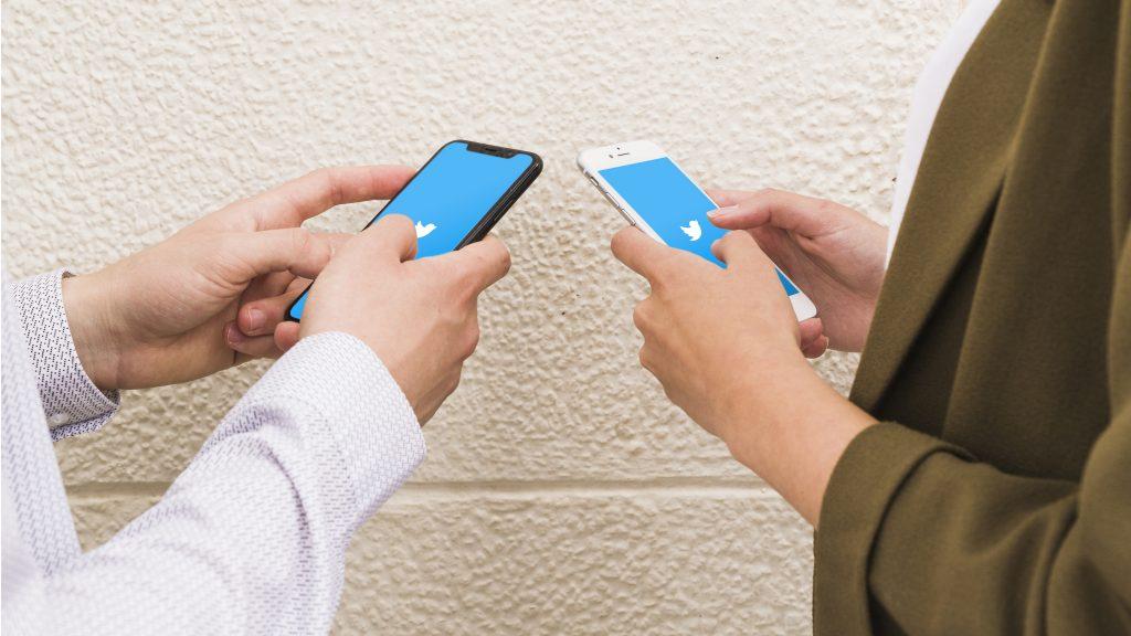 Deux personnes utilisant Twitter sur leur smartphone.