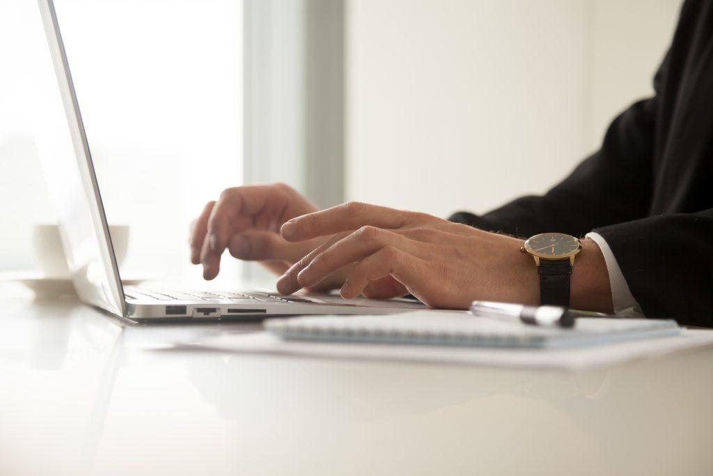 Homme qui tape sur un ordinateur portable. Quelle est la longueur idéale d'un texte pour optimiser son référencement naturel ?