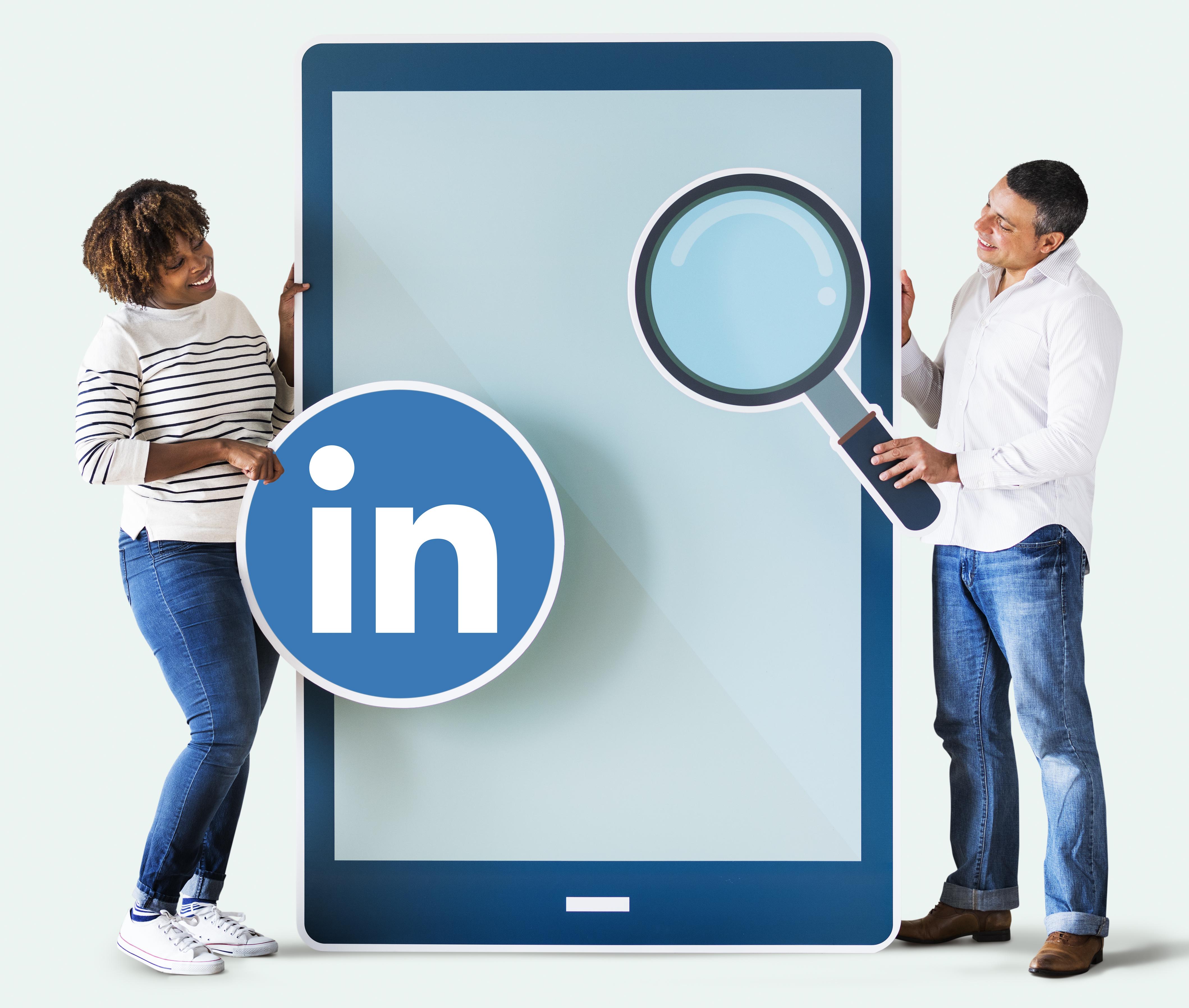 Deux personnes s'appuyant sur une tablete tactile et tenant le logo LinkedIn ainsi qu'une loupe.